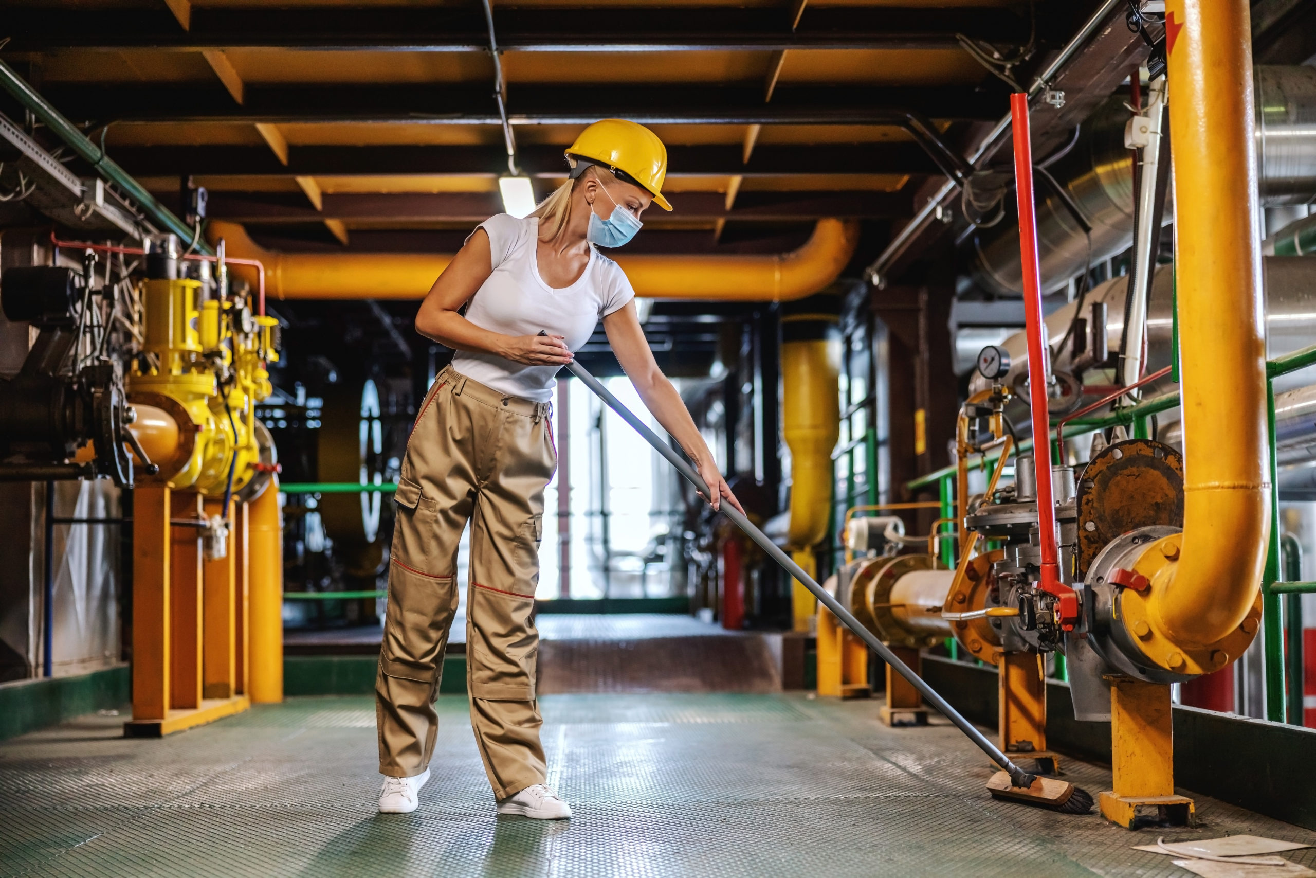 Tidy hardworking female worker in working suit with protective helmet on head and face mask brooms heating plant facility during corona outbreak.