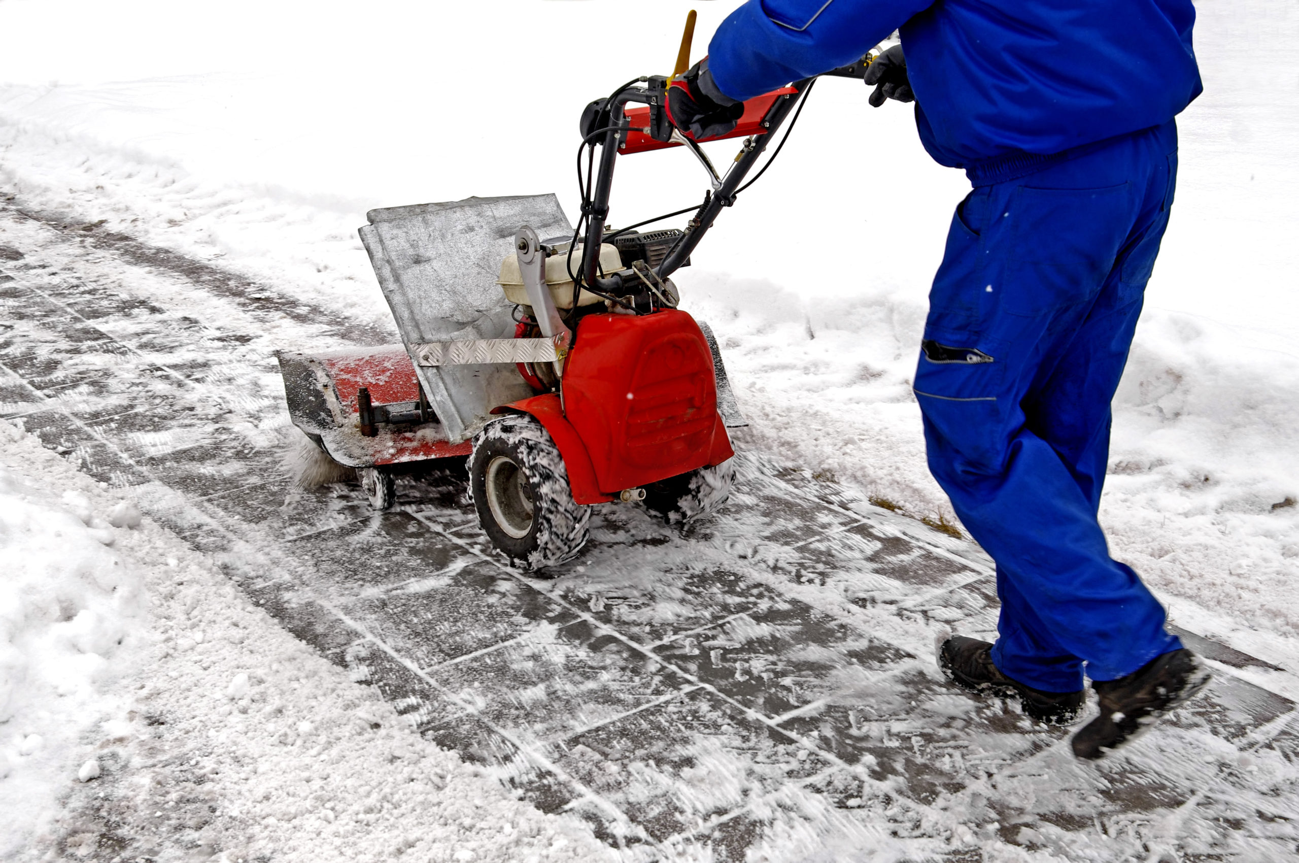 Man working with a snow blowing machine v